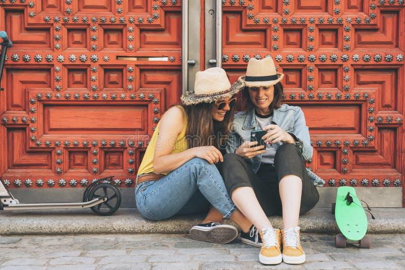 Пары привлекательных и крутых женщин лесбосские смотря мобильный телефон и усмехаясь один другого в красной предпосылке двери Так стоковое изображение