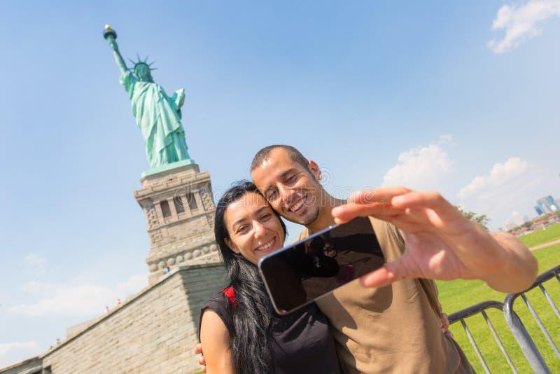 Пары принимая Selfie с статуей свободы стоковые фотографии rf