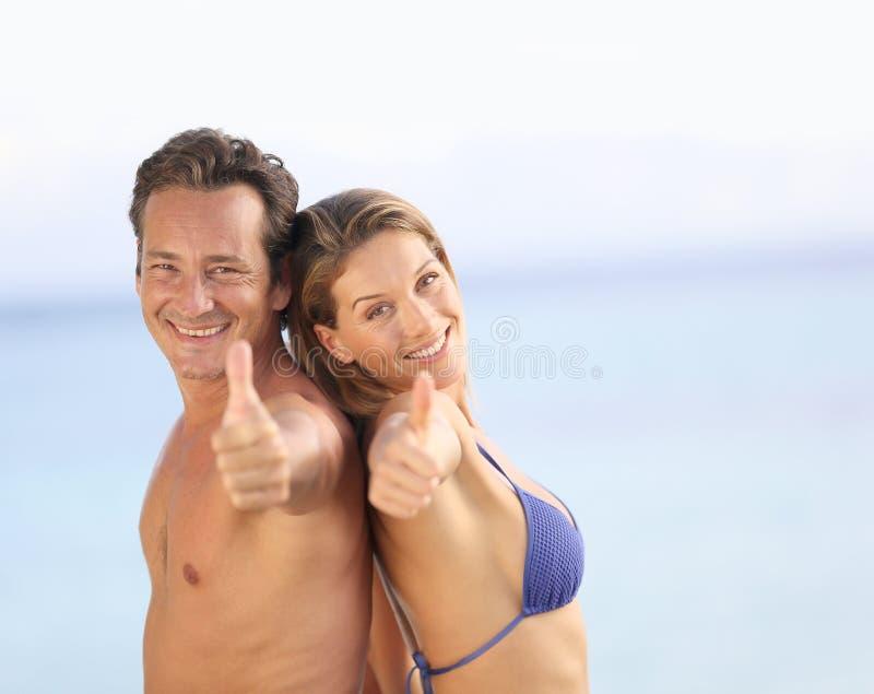 Пары при большие пальцы руки вверх наслаждаясь их праздниками стоковые фото