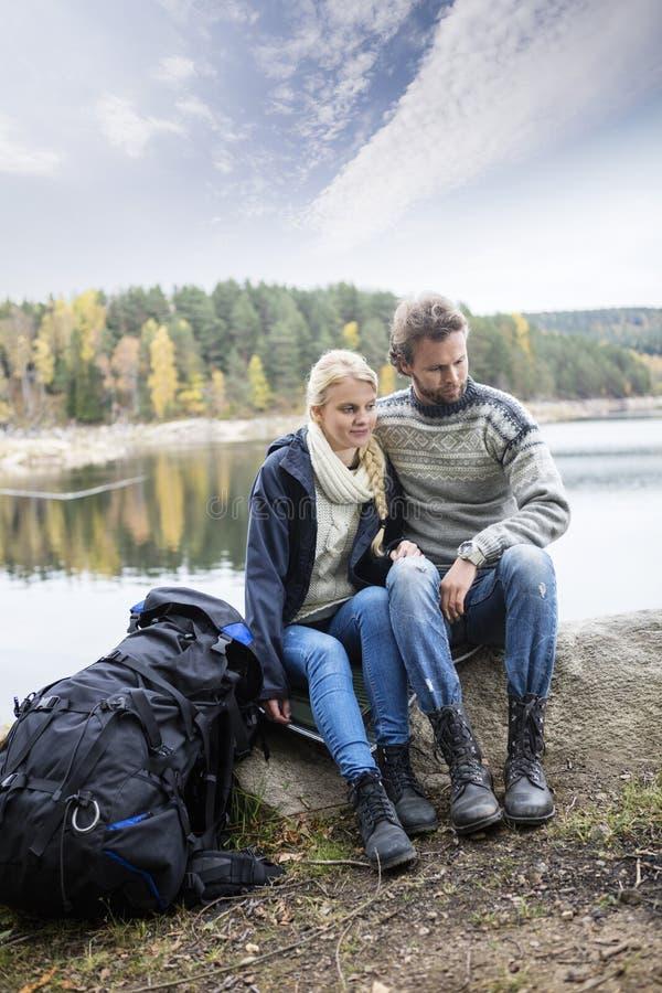 Пары при рюкзак ослабляя дальше Lakeshore во время располагаться лагерем стоковые фотографии rf