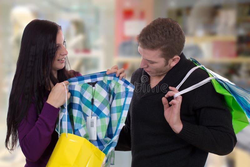 Пары при хозяйственные сумки покупая одежды в магазине одежды стоковые изображения