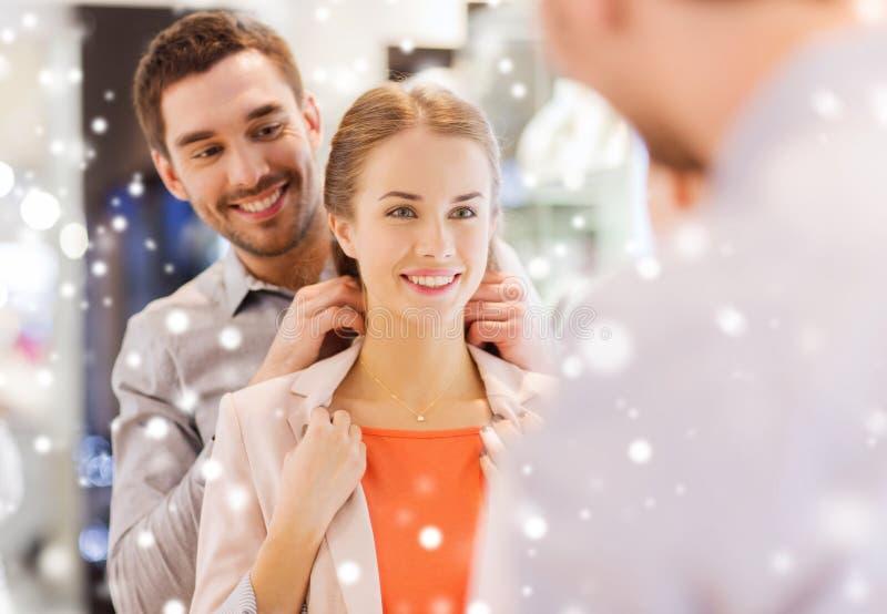 Пары пробуя золотой шкентель дальше на ювелирном магазине стоковая фотография
