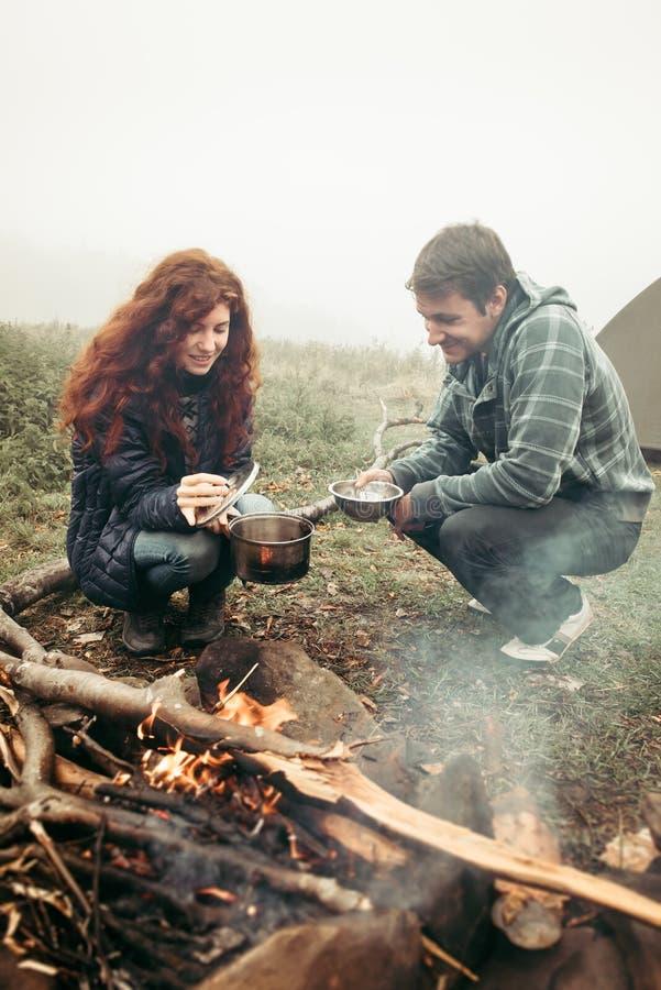 Пары путешественников варя еду на огне стоковая фотография rf