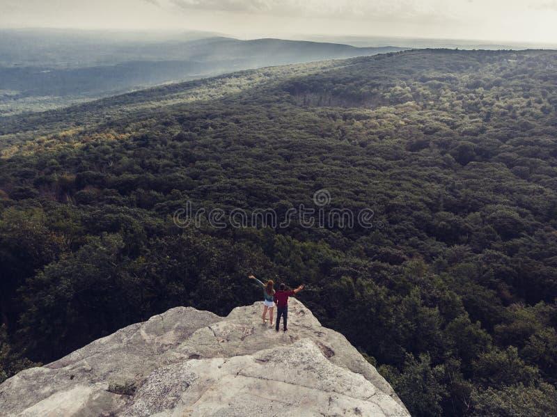 Пары путешествуют и стойка на крае скалы наслаждается взглядом к лесу природы стоковая фотография