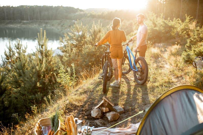 Пары путешествуя с велосипедами и шатром в горах стоковые изображения
