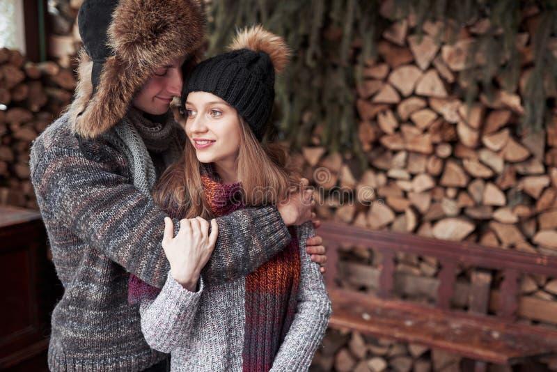 Пары рождества счастливые в объятии влюбленности в лесе снежной зимы холодном, космосе экземпляра, торжестве партии Нового Года,  стоковые фото