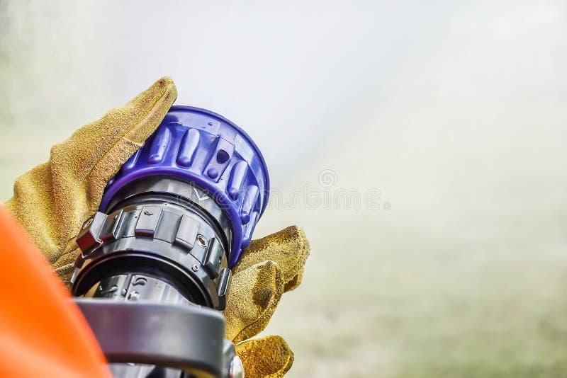 2 пары рук держа ручку на конце пожарные мочат воду шланга распыляя во время практики стоковые фотографии rf
