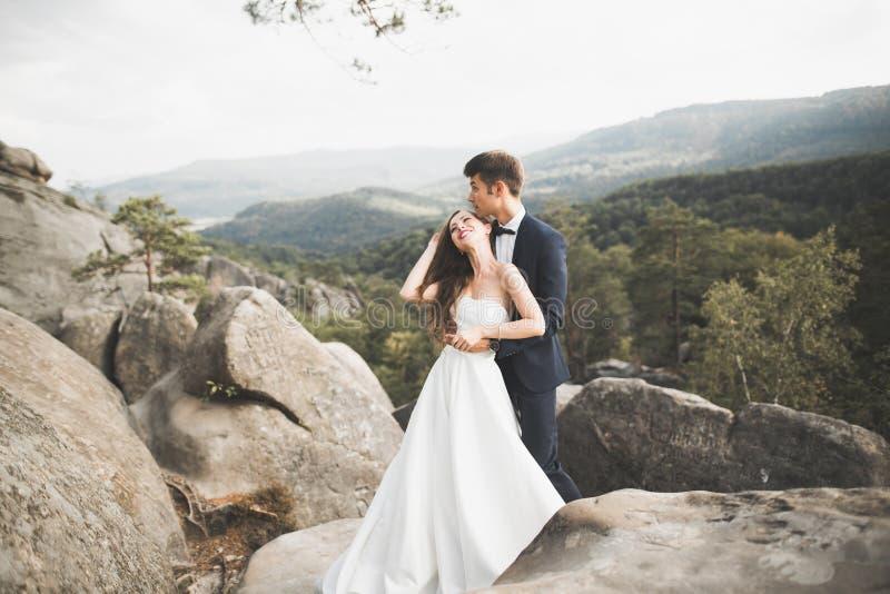 Пары свадьбы в влюбленности целуя и обнимая около утесов на красивом ландшафте стоковые изображения