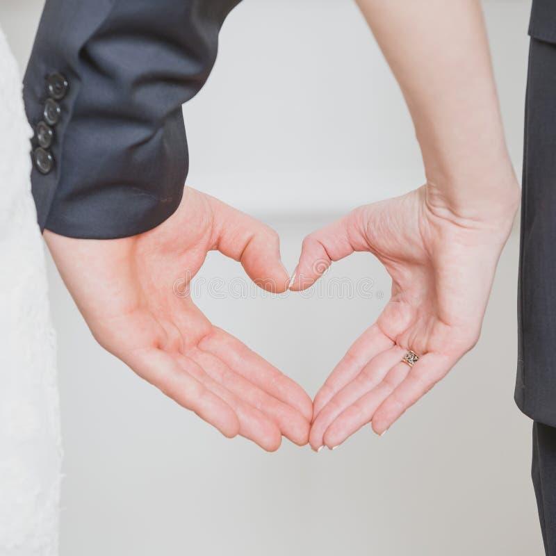 Пары свадьбы показывая форму сердца от их рук стоковые фото