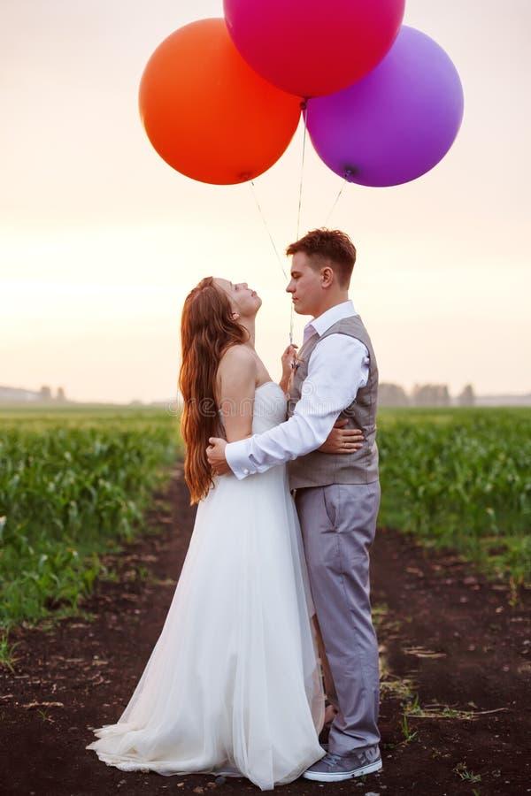 Пары свадьбы на поле с большими воздушными шарами стоковые изображения