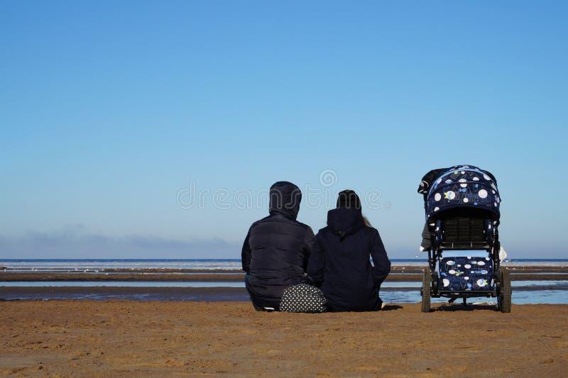 Пары семени с детской дорожной коляской сидят на пляже весной стоковое изображение rf