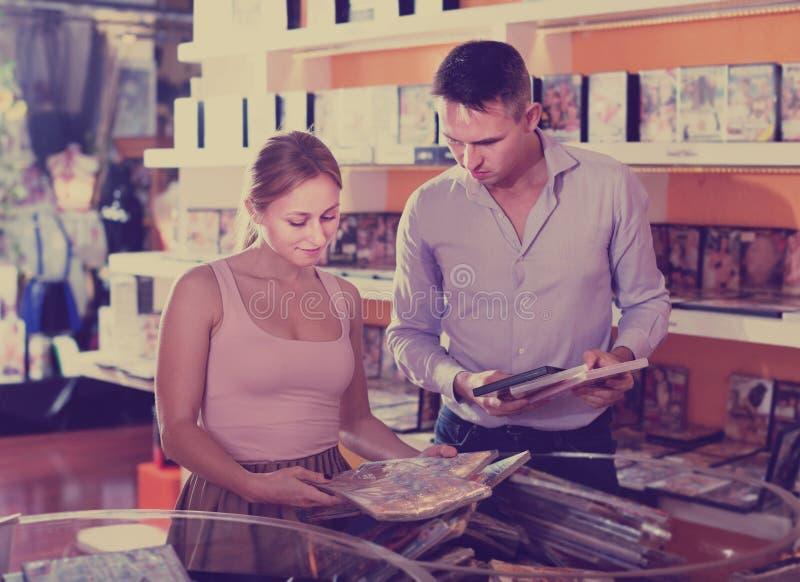 Пары семьи выбирая эротичное видео в магазине внутри помещения стоковое изображение rf