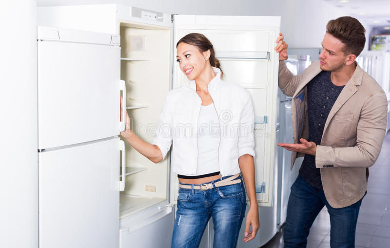 Пары семьи среднего класса выбирая новый холодильник стоковая фотография