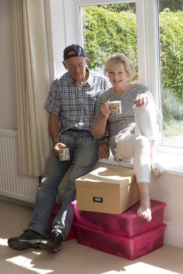 Пары сидя на кофе сиденья у окна выпивая стоковое фото