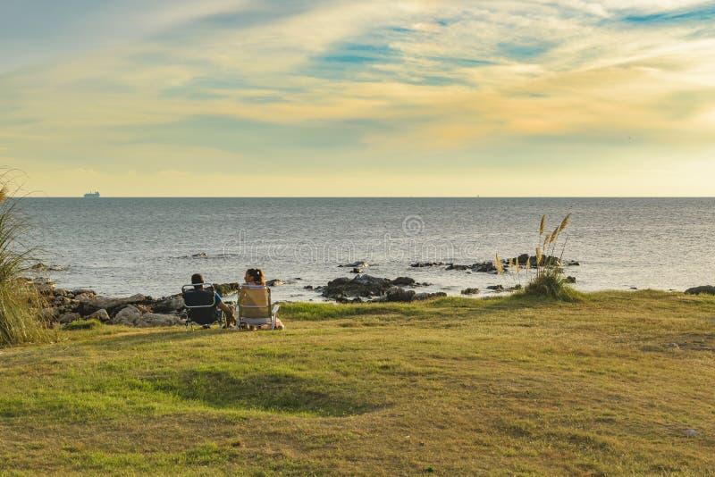 Пары сидя на парке портового района стоковые изображения