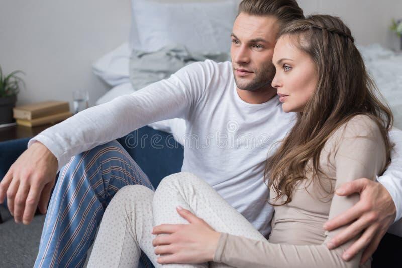 Пары сидя на поле в пижамах и полагаться стоковые фотографии rf