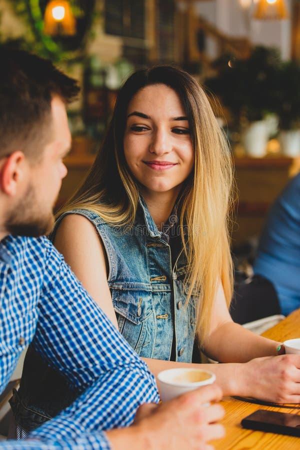 Пары сидя на таблице в кафе и выпивая кофе стоковые изображения rf