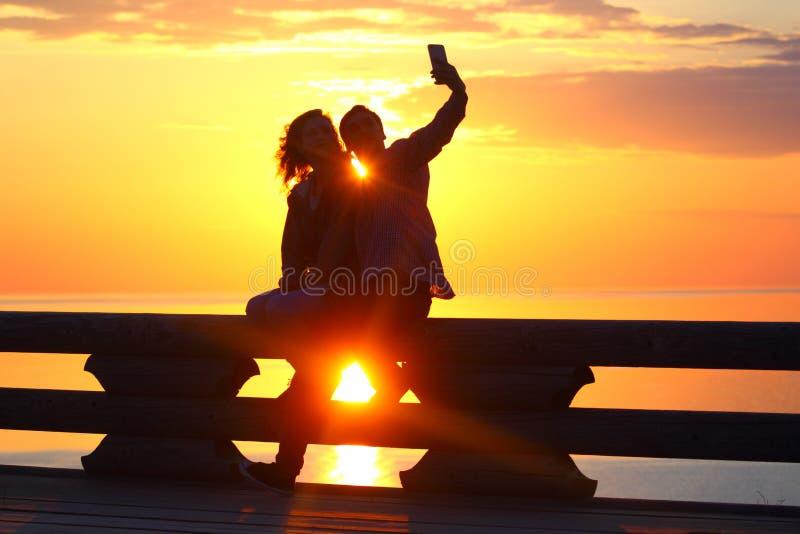 Пары силуэта молодые на заходе солнца морем Selfie стоковая фотография rf