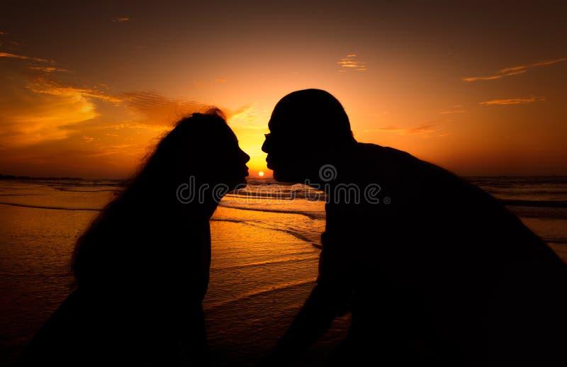 Пары силуэта целуя над предпосылкой захода солнца стоковое фото rf