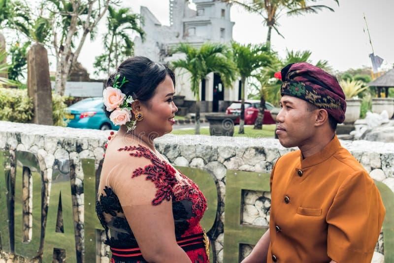 Пары симпатичного медового месяца балийские в традиционных одеждах совместно в природе человека kuta острова bali городок захода  стоковое фото