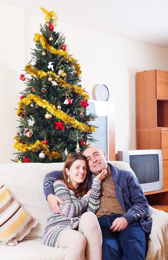 Пары сидя на софе на времени рождества стоковые изображения