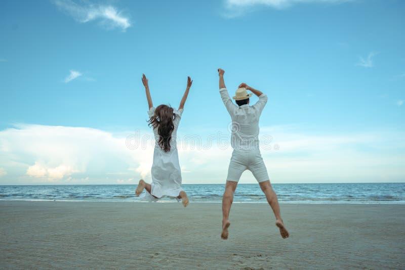 Пары скача на пляж стоковые фото