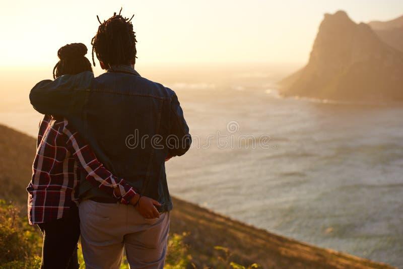 Пары смешанной гонки стоя совместно наблюдающ взгляд от позади стоковая фотография