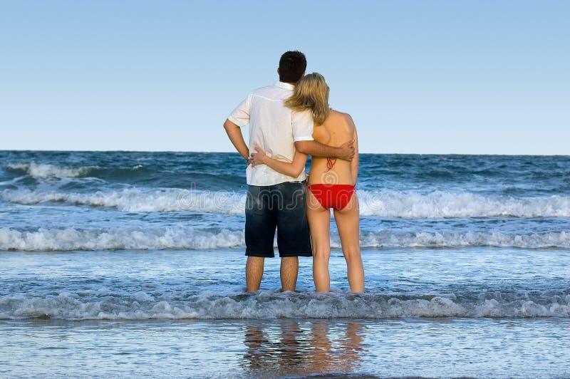 пары смотря вне море к стоковая фотография