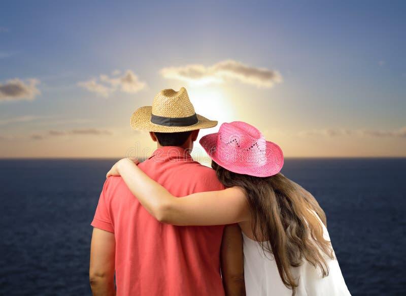 Пары смотря заход солнца на океане стоковые фотографии rf