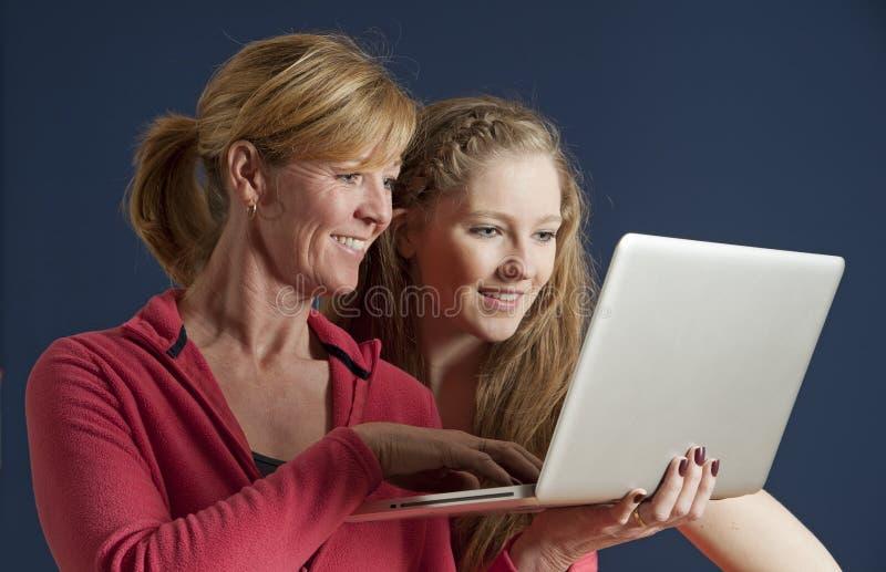 Пары смотря портативный компьютер стоковое фото