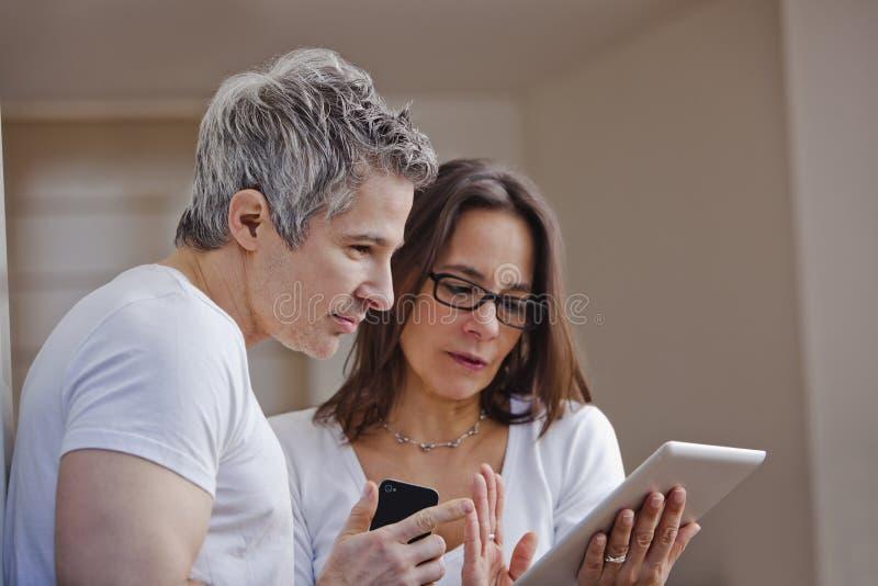 Пары смотря цифровую таблетку стоковое изображение