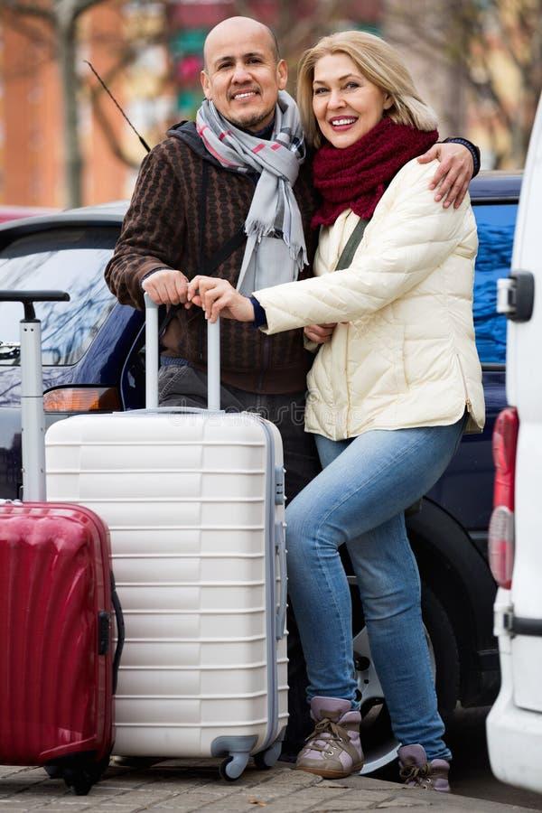 Пары старшия усмехаясь приятные путешественников представляя с troller стоковые фотографии rf