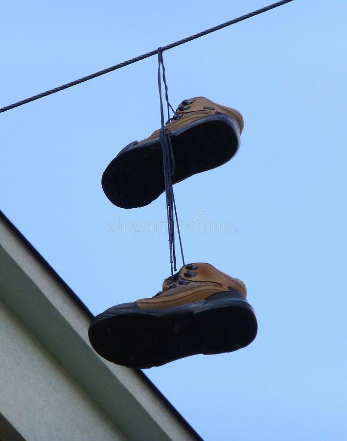 Пары старых коричневых ботинок вися на проводе стоковые фотографии rf