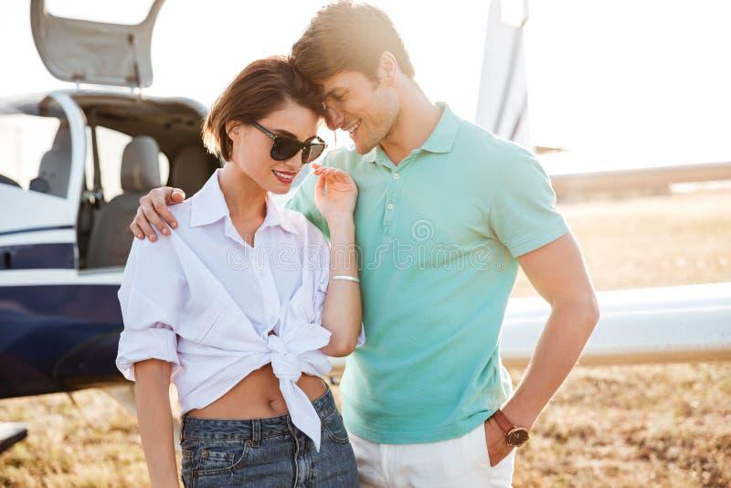Пары стоя и обнимая около малого самолета стоковое изображение
