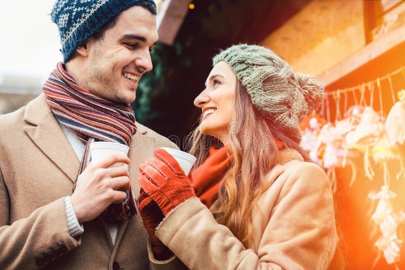 Пары стоя на рождественской ярмарке перед стойлом подарка стоковая фотография rf