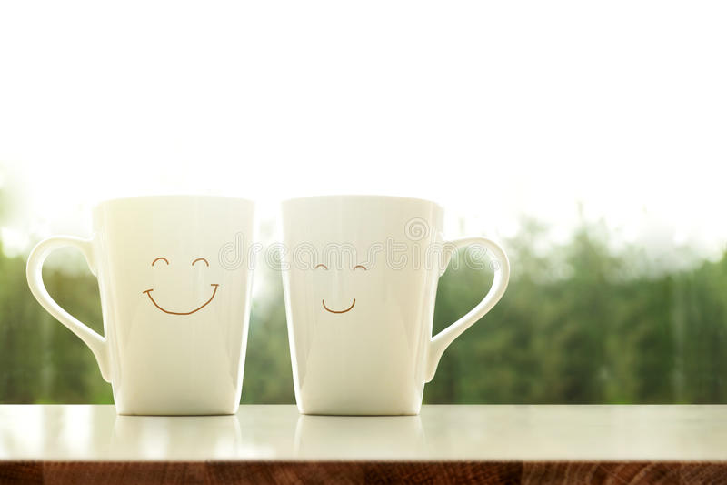Пары счастливой кружки кофе с стороной в утре, нерезкостью smiley стоковые фото