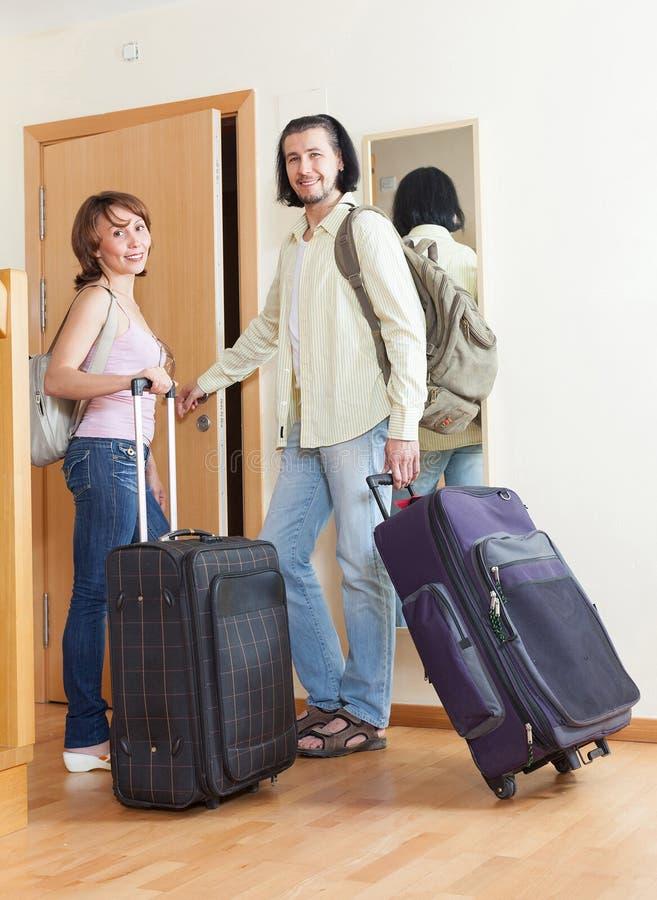 Пары с багажом в доме идя на длинные каникулы стоковые изображения