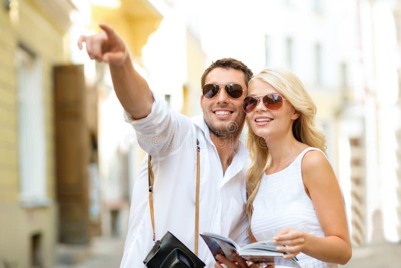 Пары с гидом карты, камеры и путешественников стоковое изображение