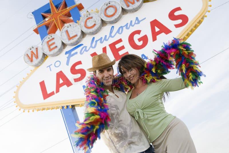 Пары с горжеткой против «гостеприимсво к знака Лас-Вегас» стоковые изображения