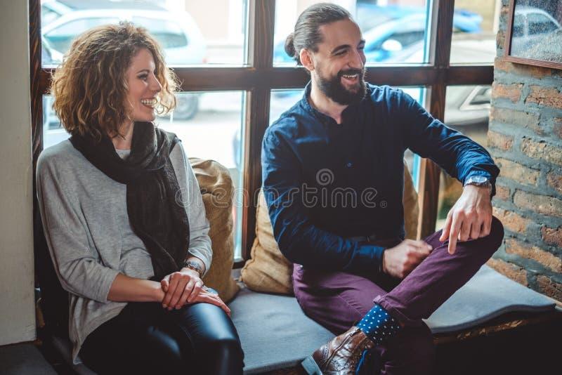Пары с окном за сидеть и смеяться над стоковые фото