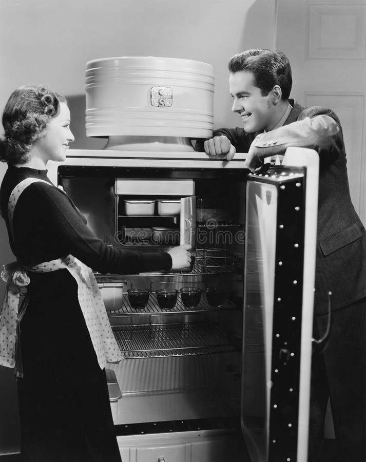 Пары с открытым холодильником (все показанные люди более длинные живущие и никакое имущество не существует Гарантии поставщика ко стоковая фотография rf