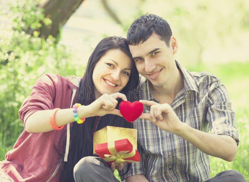 Пары с подарком на зеленой траве стоковые изображения rf