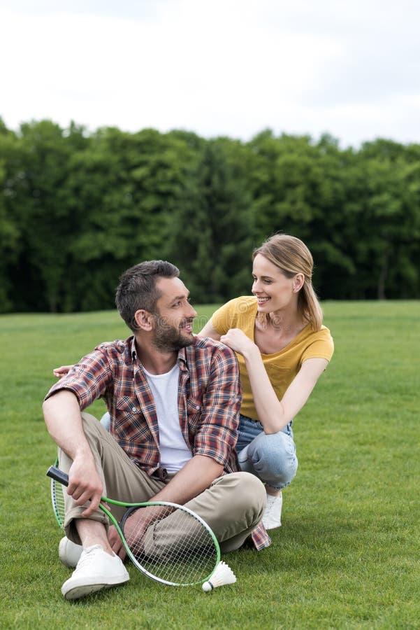 Пары с ракеткой бадминтона и shuttlecock отдыхая на траве стоковое изображение