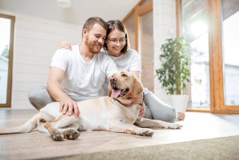 Пары с собакой в доме стоковое изображение