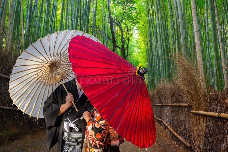 Пары с традиционными японскими зонтиками представляя на бамбуковом лесе в Arashiyama стоковое фото rf