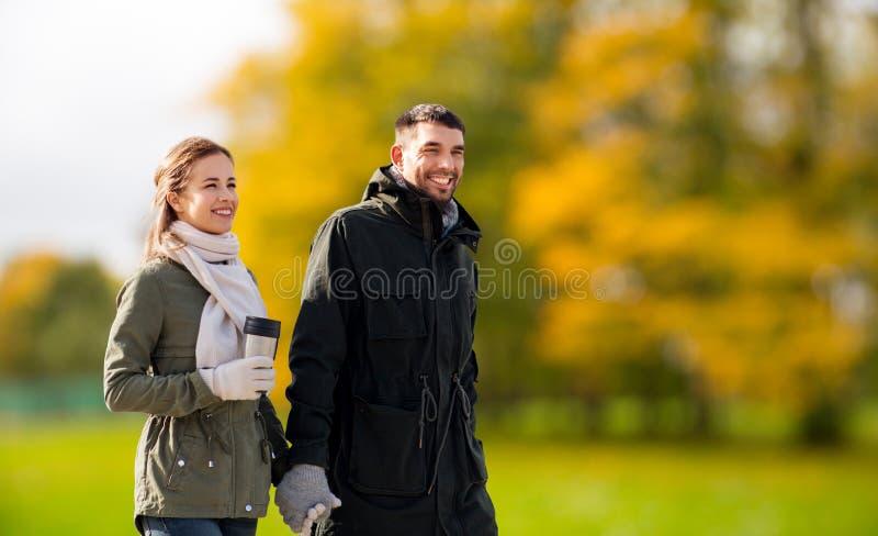 Пары с tumbler идя вдоль парка осени стоковая фотография rf