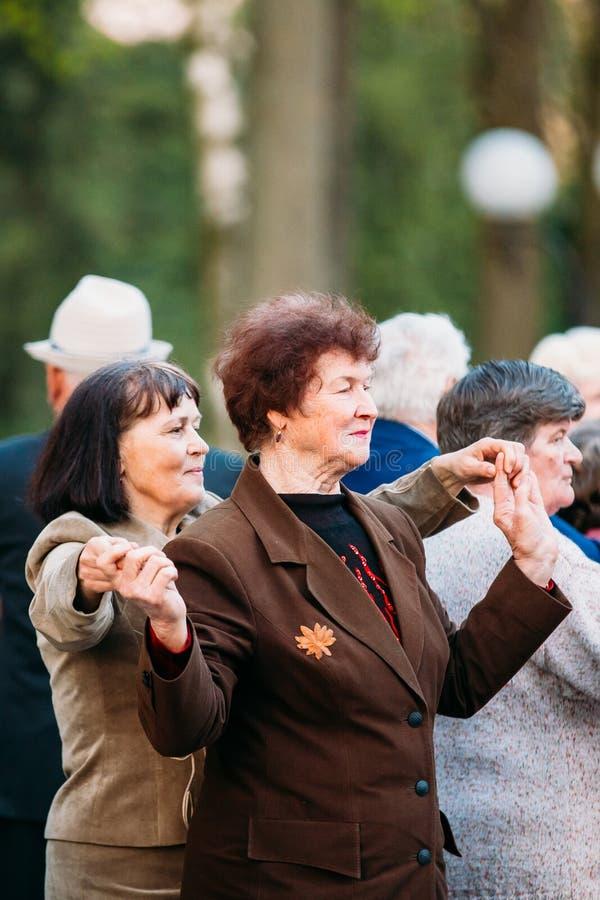 Пары танцев в летах на внешней танцплощадке среди танцевать Solus престарелое в парке атракционов лета в Gomel стоковые изображения
