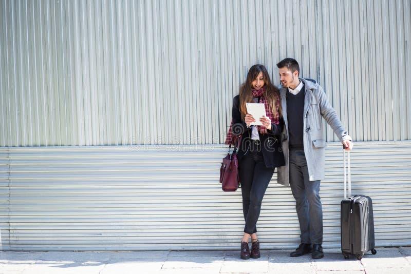 Пары туристов используя планшет в улице стоковое изображение rf