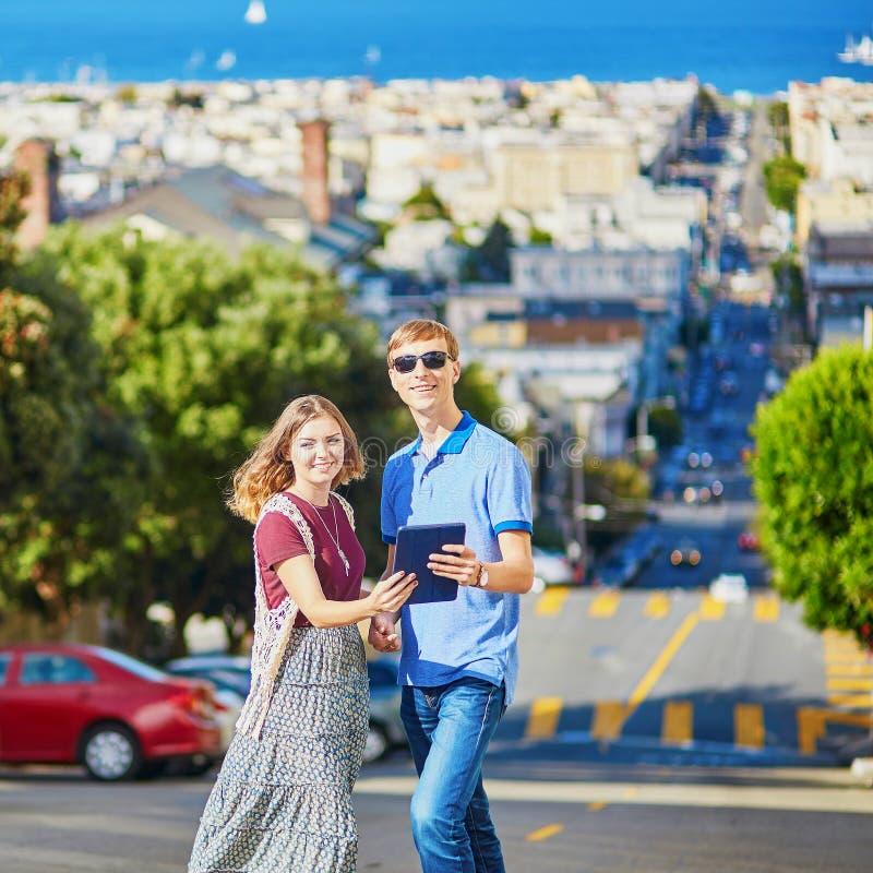 Пары туристов используя таблетку и планирующ их распорядок в Сан-Франциско, Калифорнии, США стоковая фотография rf