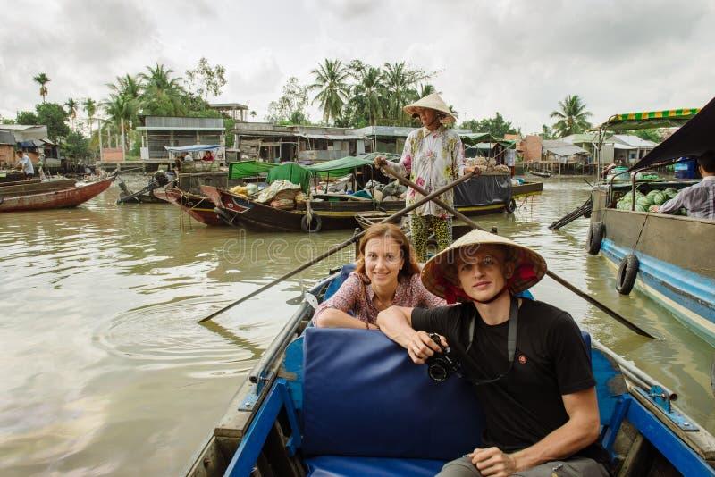 Пары туристов на плавая рынке в Вьетнаме стоковые изображения